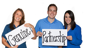"BKS Colleagues holding signs that read ""genuine"" and ""partnership"""