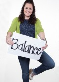 "BKS Director of Risk Management, Camille Zutes, stands on one foot while holding sign that reads ""Balance"""