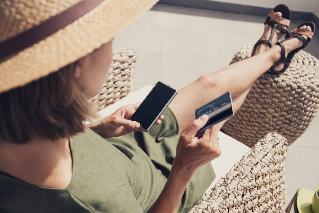 Young woman on vacations using smart phone and credit card. Online shopping concept