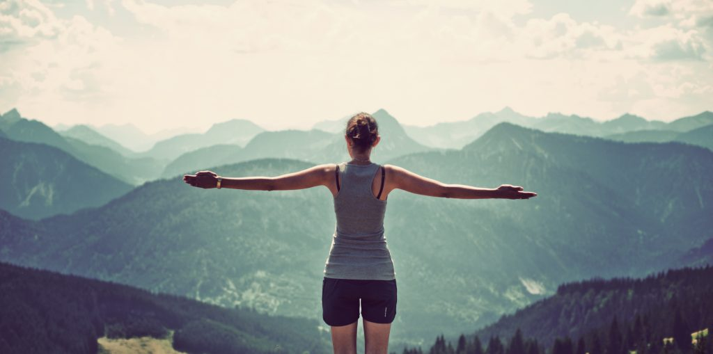Woman celebrating nature and reaching the summit of a mountian