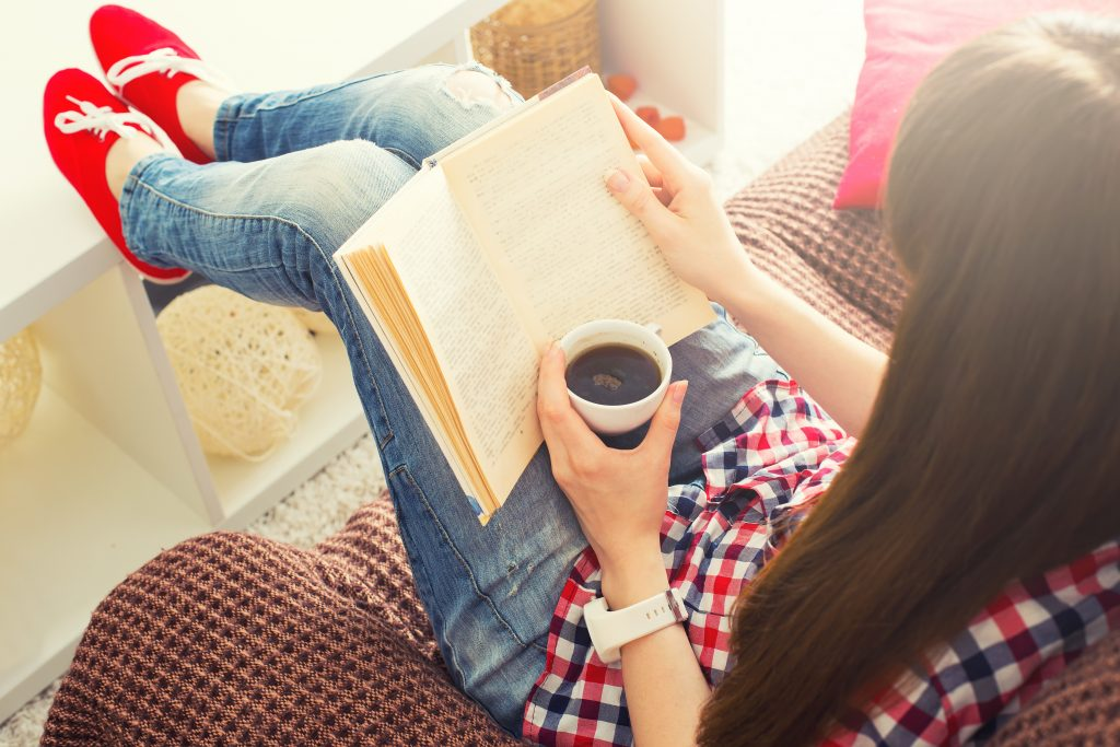 Woman sitting on the sofa reading a book holding her coffee mug
