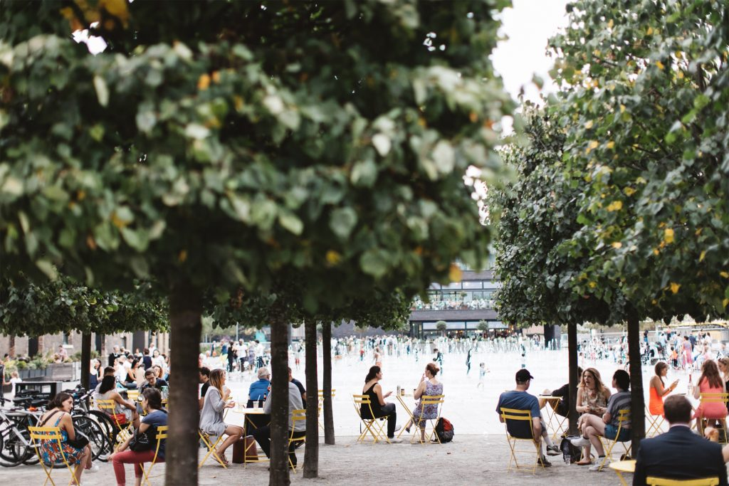 View of many people having conversations at tables between trees