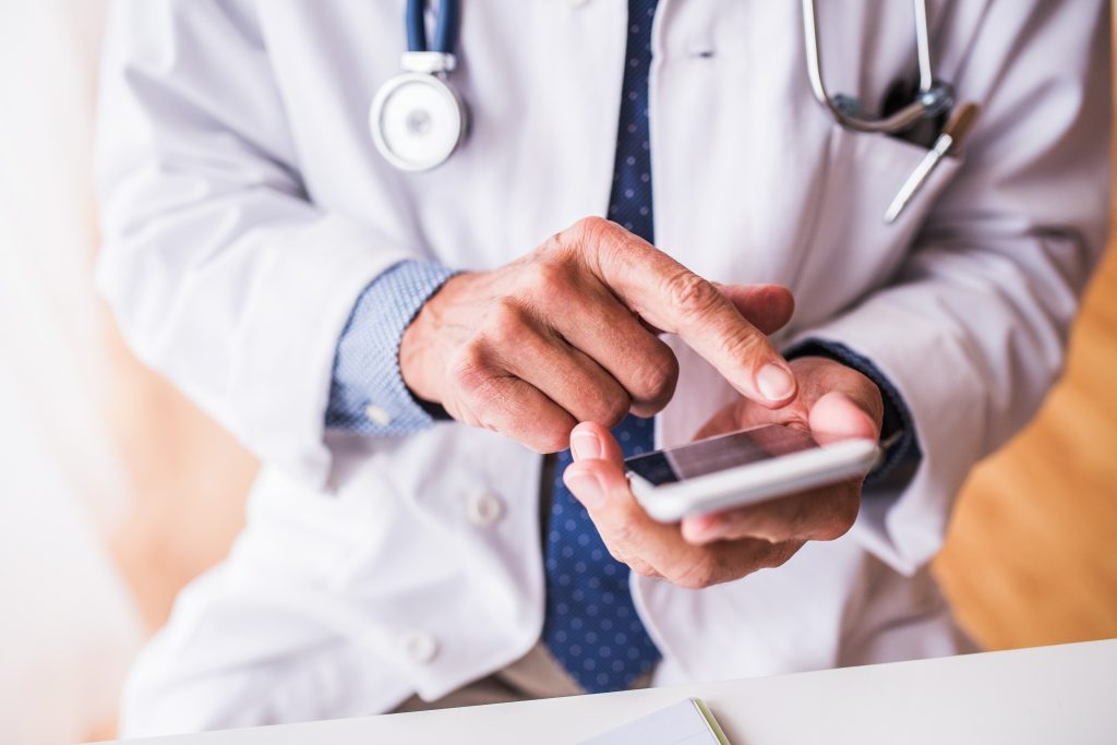Unrecognizable senior male doctor with smartphone at the office, text messaging.