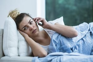 Sick woman on sofa with phone utilizes telemedicine benefits