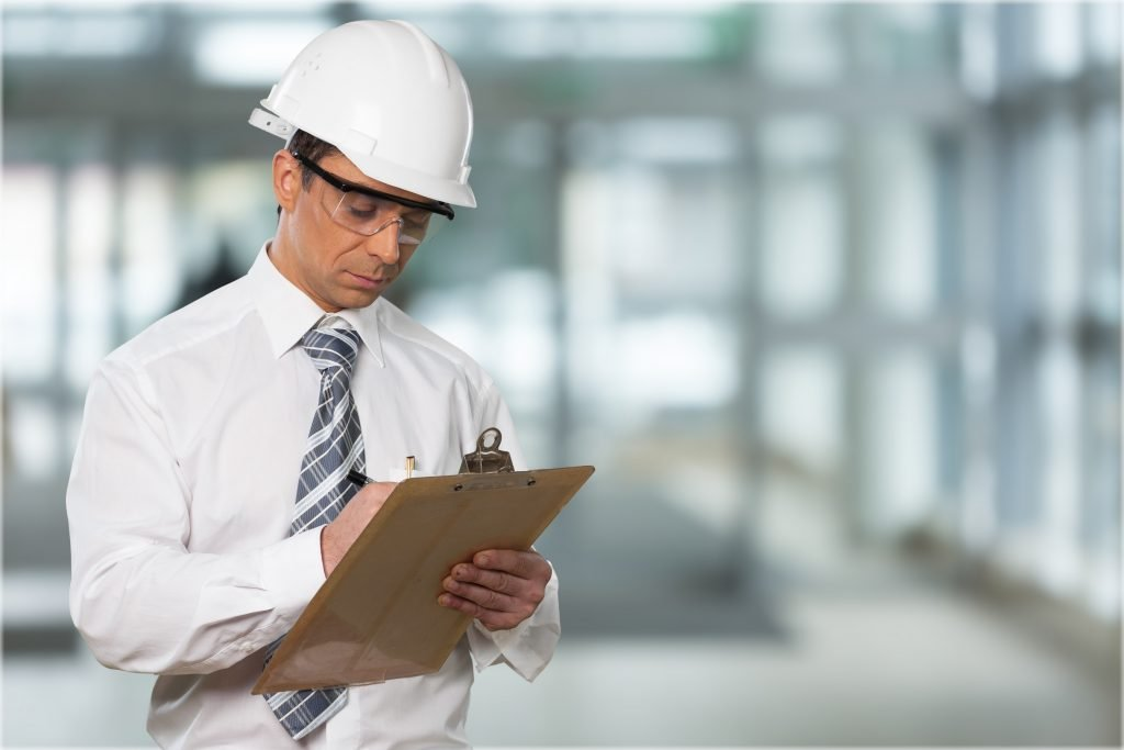 osha compliance officer with clipboard on site for osha inspection