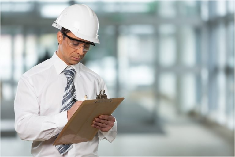 Industrial inspector wearing hardhat and writing on clipboard