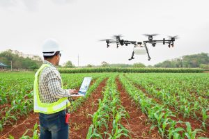 Man in hard hat and vest flies a drone over a farm to collect data on his crops.