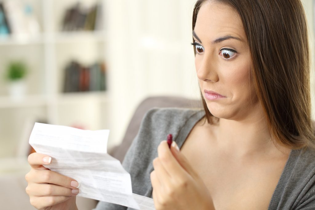 Confused woman holding pill and confused by health insurance paperwork