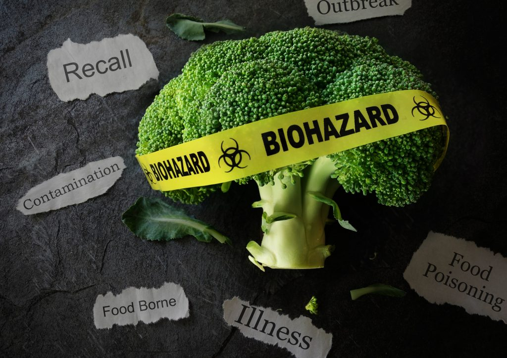 Yellow Biohazard tape on a piece of broccoli with various food poisoning related news headlines
