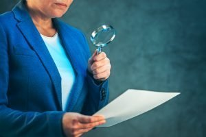 retirement plan fiduciary closely review paperwork with a magnifying glass
