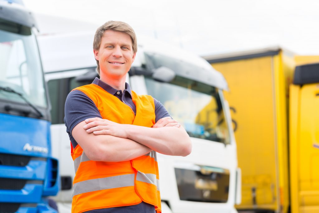 A professional vehicle operator stands in front of fleet of trucks