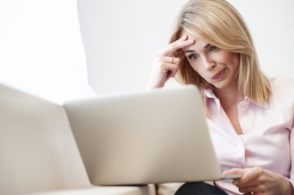 confused looking woman works on laptop