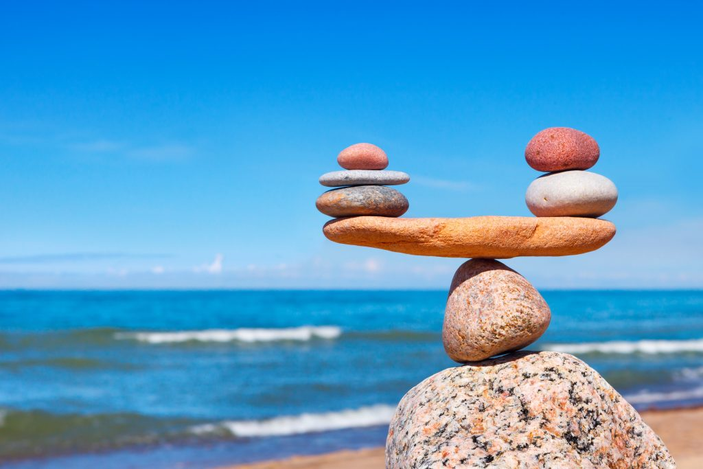 small rocks balancing on larger rocks similar to a scale with a beach in the background.