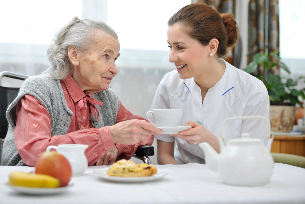 Female nurse provides senior woman with breakfast meal and care
