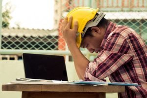Surety bonding: Contractor is tense and frustrated on the construction site with his forms and computer.