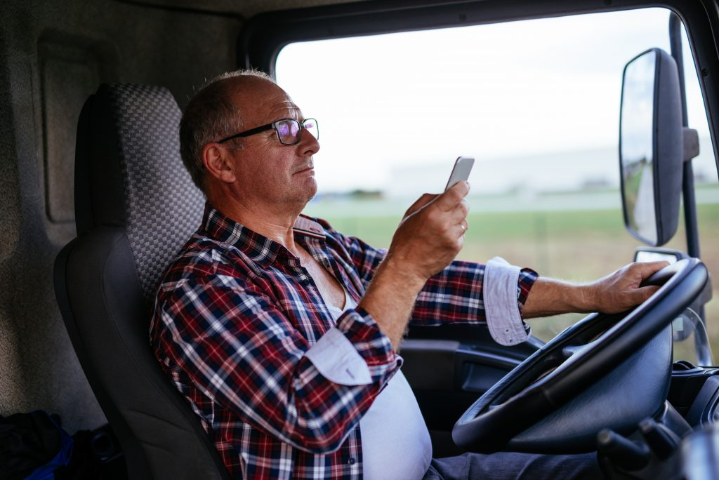 Man driving in commercial delivery truck is distracted by mobile device.