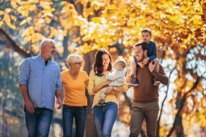 a multi-generational family walks through a wooded area on an Autumn day