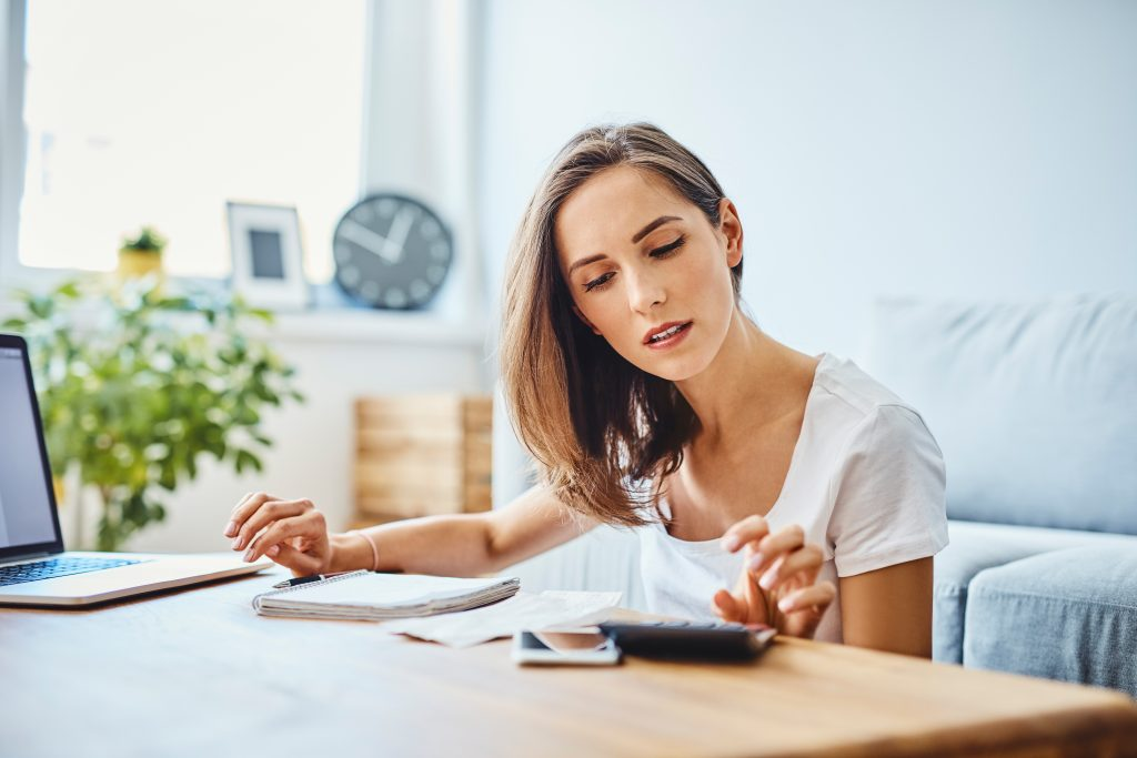 millennial woman practicing financial wellness at home with pc and calculator