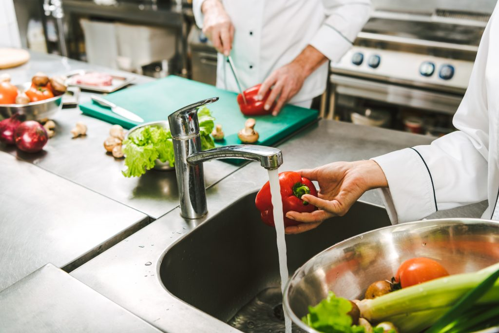 chefs practicing food safety in restaurant kitchen by cleaning vegetables