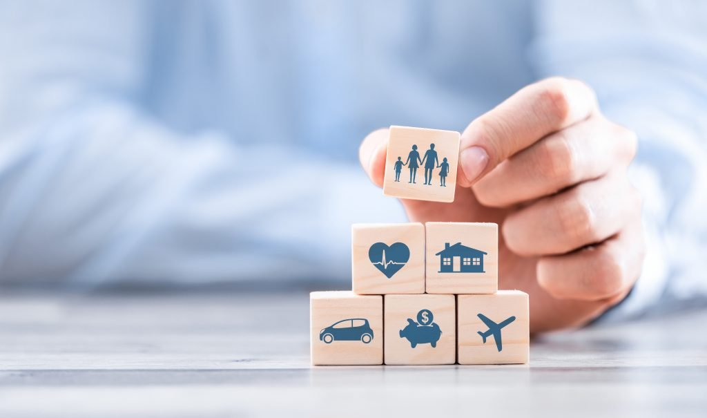 man stacking blocks with home medical car plane icons represents holistic approach to risk management
