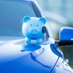auto insurance savings in blue piggy bank on blue car