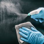 close up of hands cleaning window with spray covid-19 response services