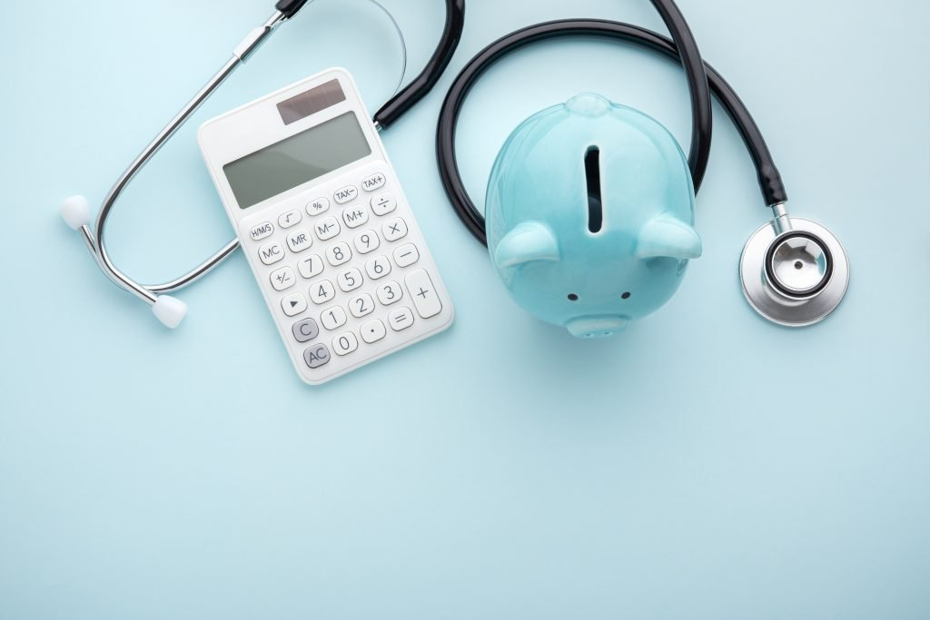 light blue piggy bank with stethoscope and calculator