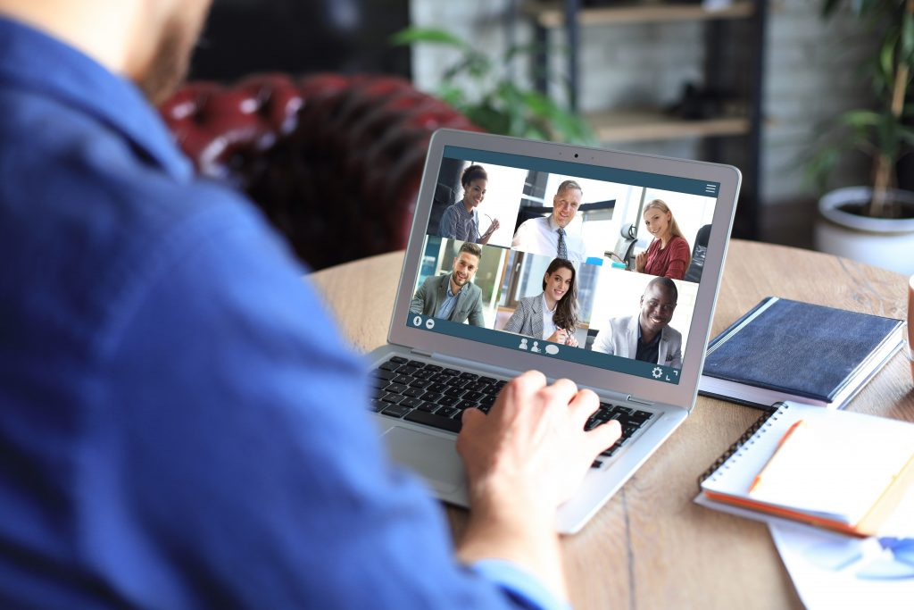 man engaged in video conference with colleagues on laptop