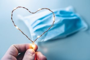 blue cloth face mask with light up heart in foreground
