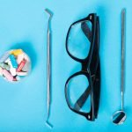 cup of prescription pills dental tools and glasses symbolize ancillary benefits