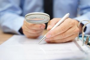 private equity professional analyzing documents with magnifying glass for m&a due diligence